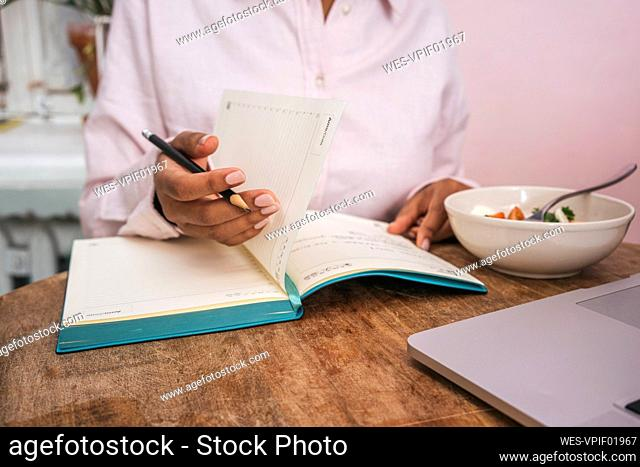 Close-up of young woman taking notes at table