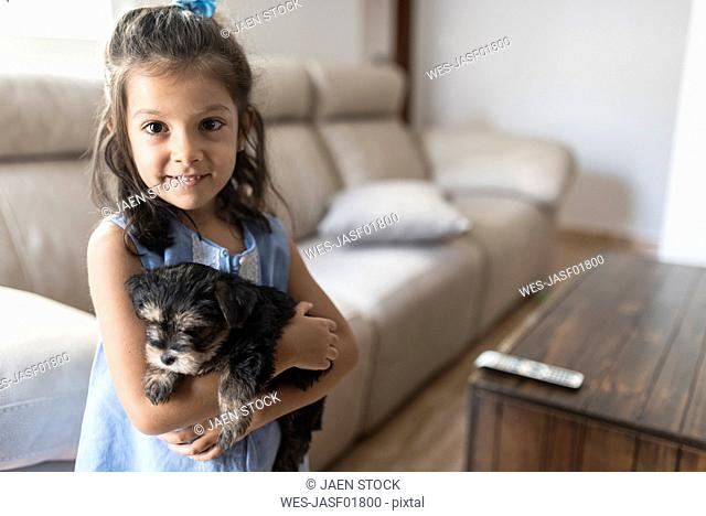 Portrait of smiling little girl with her puppy at home