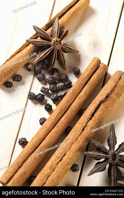 Spices and herbs. Food and cuisine ingredients. Cinnamon sticks, anise stars and black peppercorns on a wooden background