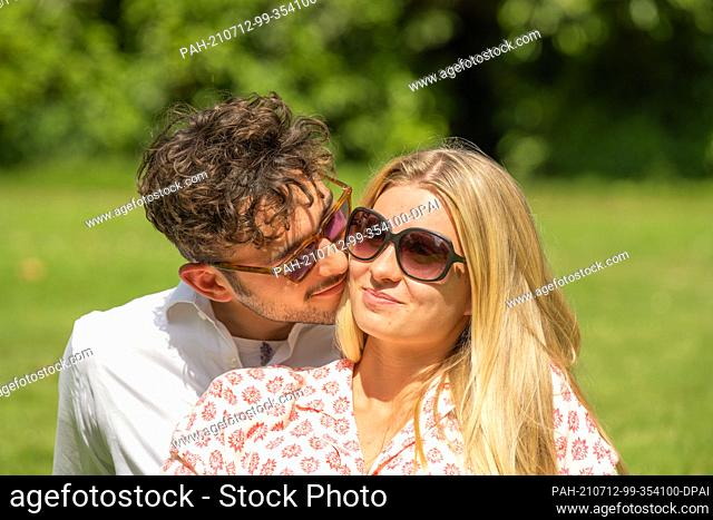 PRODUCTION - 03 July 2021, Lower Saxony, Oldenburg: ILLUSTRATION - A woman and a man sit together in the grass in a park (posed scene)