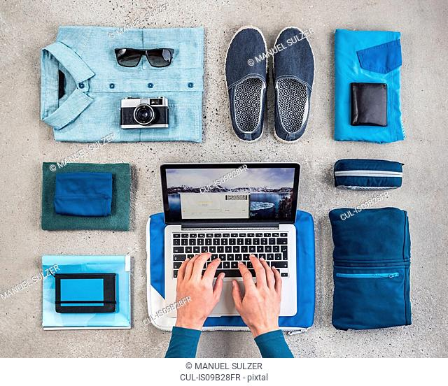 Overhead view of man's hands typing on laptop surrounded by travel packing items, with blue shirt, retro camera, wash bag and notebook