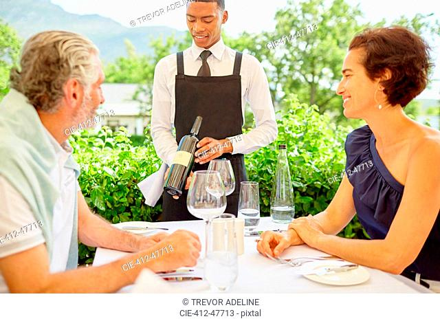 Wine steward showing wine bottle to mature couple dining on patio