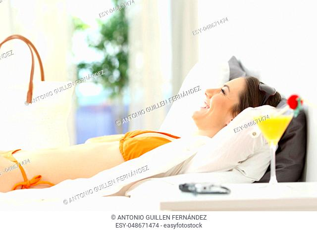 Side view portrait of a happy woman relaxing lying on a bed of an hotel room on summer vacations