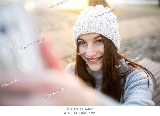 Portrait of smiling young woman taking selfie with smartphone in winter