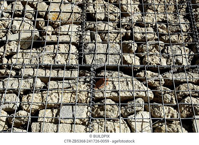 Wire mesh protecting stone wall