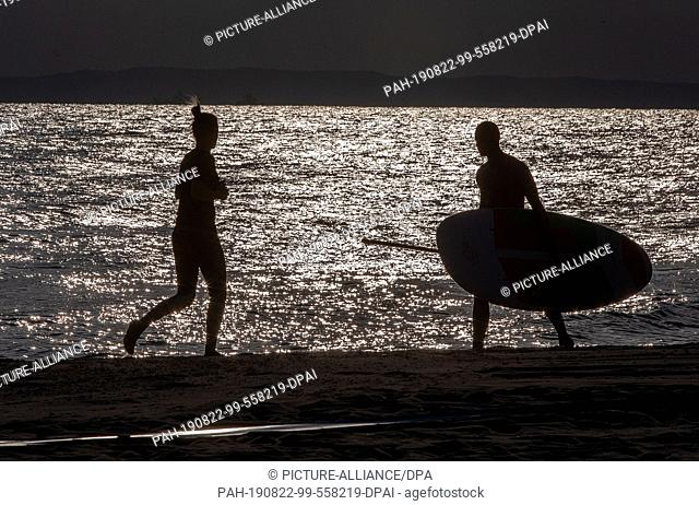 21 August 2019, Mecklenburg-Western Pomerania, Ahlbeck: A jogger and a stand-up paddler are out and about on the sports beach in the morning