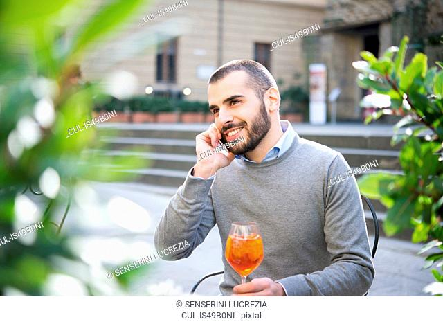 Young man sitting outside bar, holding drink, using smartphone