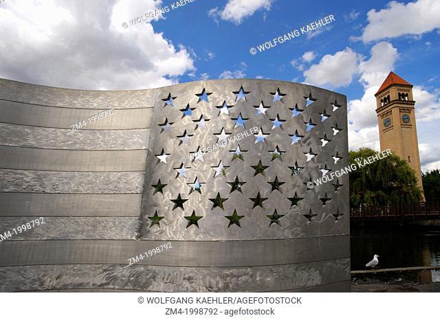 USA, WASHINGTON STATE, SPOKANE, RIVERFRONT PARK, ALUMINUM BENCH (AMERICAN FLAG) ART, CLOCK TOWER IN BACKGROUND