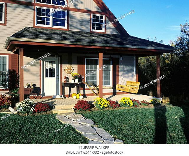 PORCH: country home with fall mums surrounding porch, porch swing, pumpkins