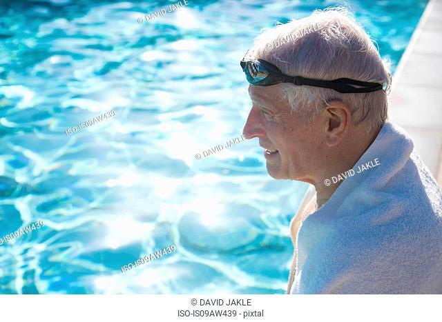 Senior man sitting on edge of outdoor swimming pool, towel around shoulders