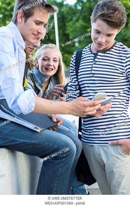 Group of friends outdoors using cell phones