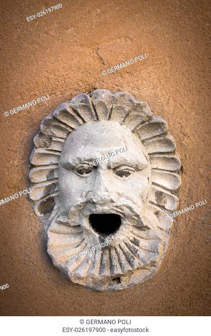Ancient marble sculpture depicting a head with an open mouth