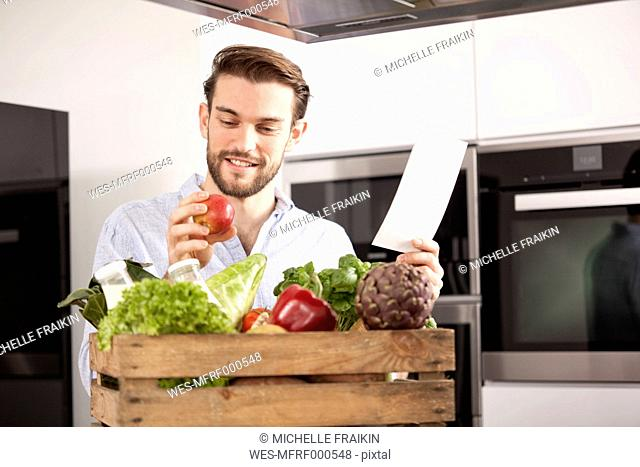Portrait of young man with wooden box of fresh vegetables and shopping list in his kitchen
