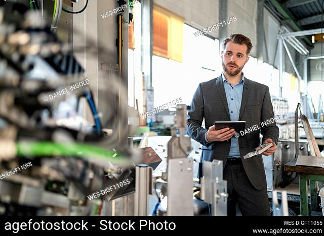 Young businessman with tablet and workpiece at a machine in a factory