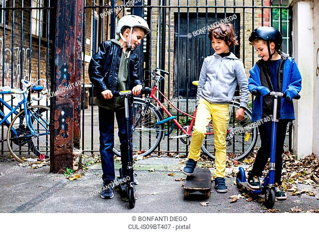 Boys riding push scooter and skateboard, bicycles in background