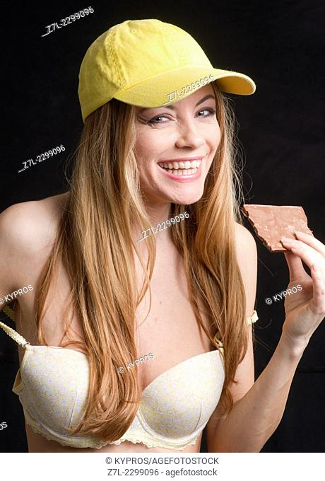 Portrait of smiling young woman in bra holding bar of chocolate