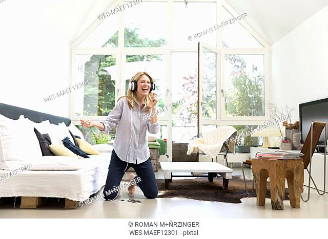 Excited woman at home listening to music
