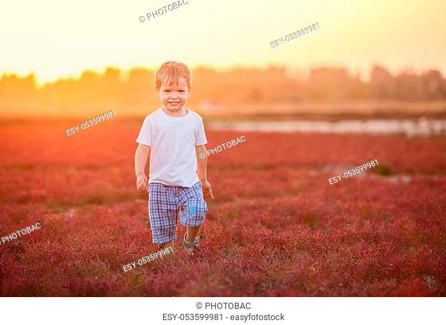 Happy little boy playing outdoors at sunset