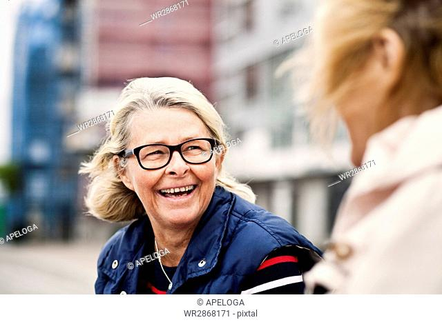 Happy senior woman looking at female friend in city
