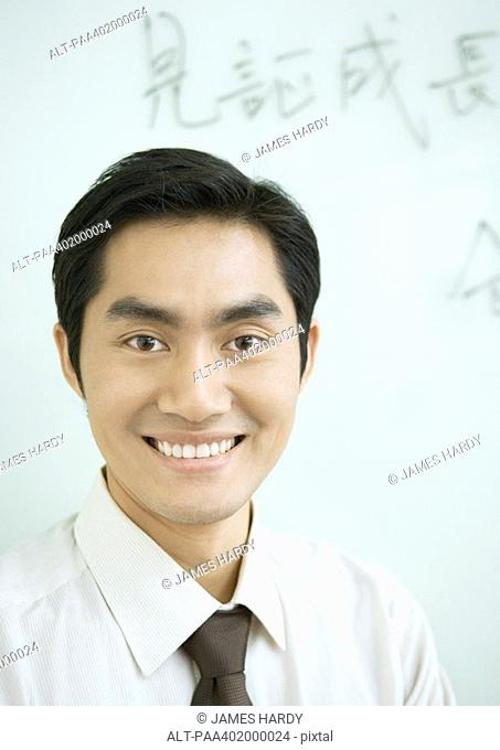 Businessman smiling, Chinese script on whiteboard in background, portrait