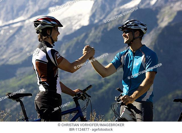 Mountainbikers congratulating each other, Northern Tyrol, Austria, Europe