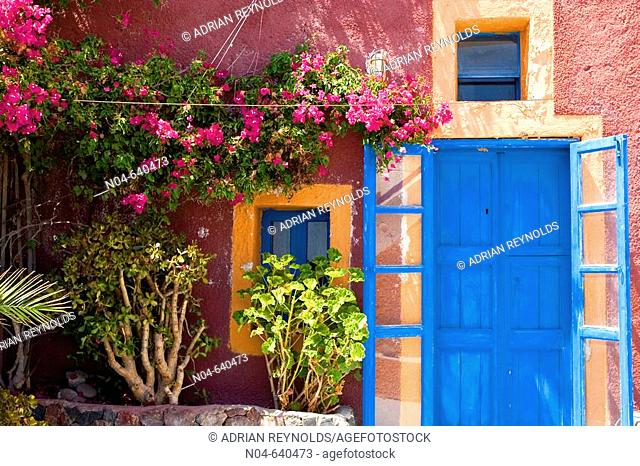 Colourful rustic house with blue door and flowers. Santorini. Greece