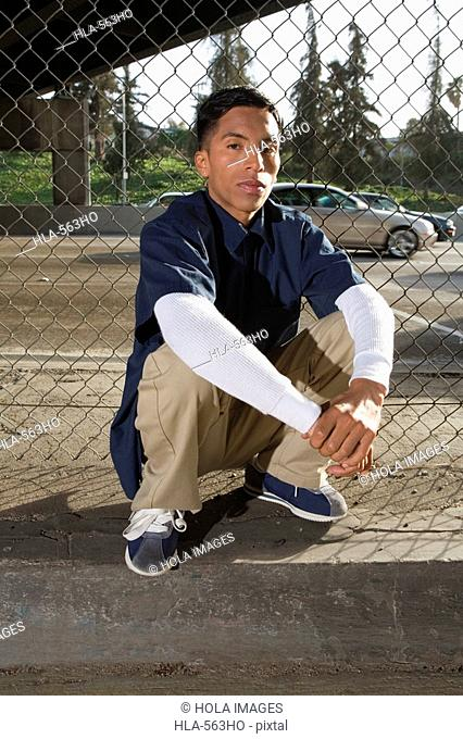 Portrait of a young man crouching in front of a chain-link fence
