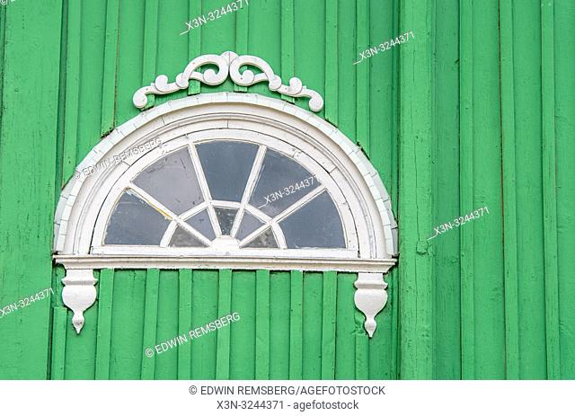 Detail view of half-circular window set in bright green wall of Russian Orthodox Church (Cerkiew Š›w. Michala Archaniola w Trzesciance) in the 'Land of the Open...
