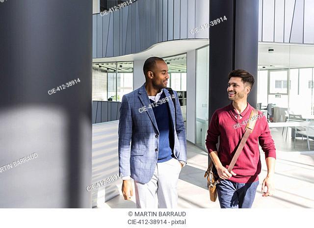 Businessmen talking and walking in modern office lobby