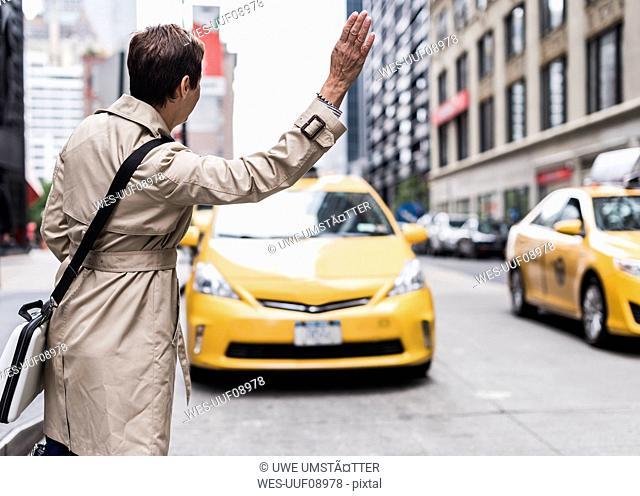 USA, New York City, woman in Manhattan hailing a taxi