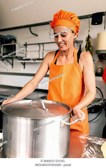 Cook with big cooking pot in the kitchen