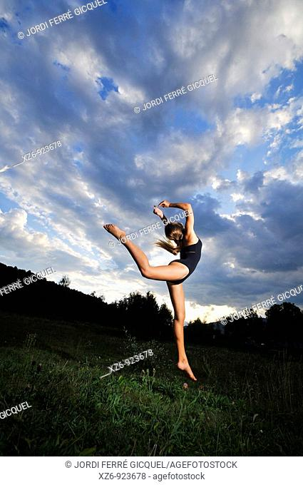 European young doing gymnastics in a meadow in the Pyrenees
