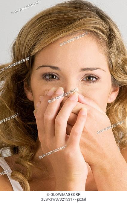 Portrait of a young woman covering her mouth with her hands