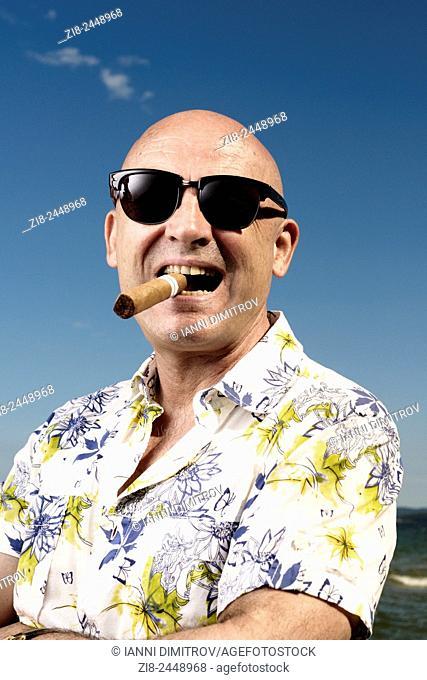 Bald man in Hawaiian shirt,sunglasses and cigar on holiday