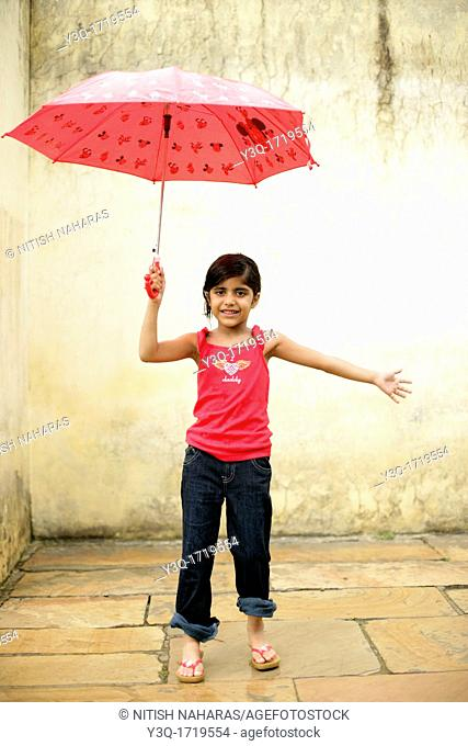 Innocent young girl smiling in the rain while holding an umbrella