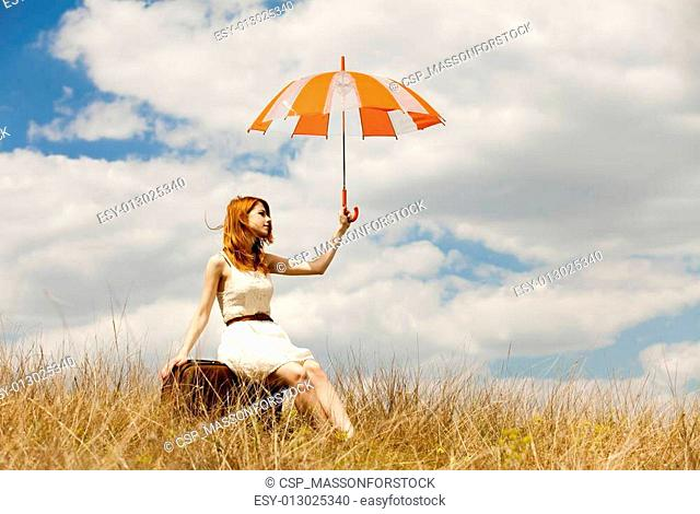 Beautiful redhead girl with umbrella and suitcase at outdoor