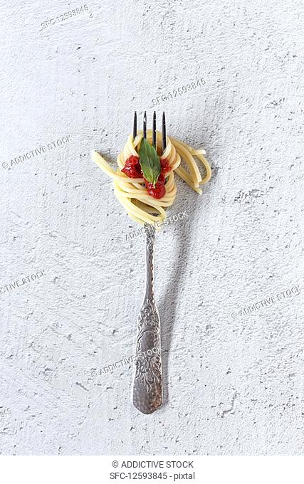 Spaghetti with tomato sauce on white background