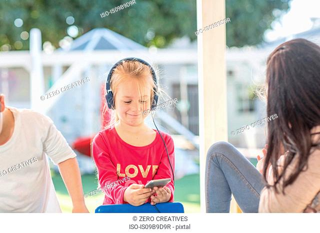 Young girl holding smartphone, wearing headphones