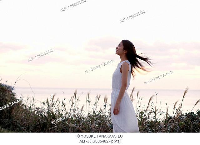 Young Japanese woman in a white dress at a cliff over the sea at sunrise, Chiba, Japan