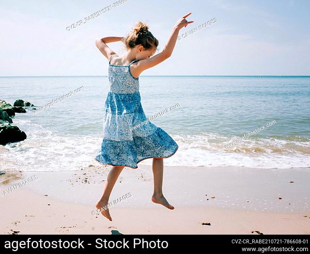 girl dancing on the beach by the sea on a sunny day in the UK