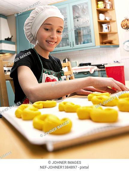 Smiling girl making traditional Swedish saffron rolls