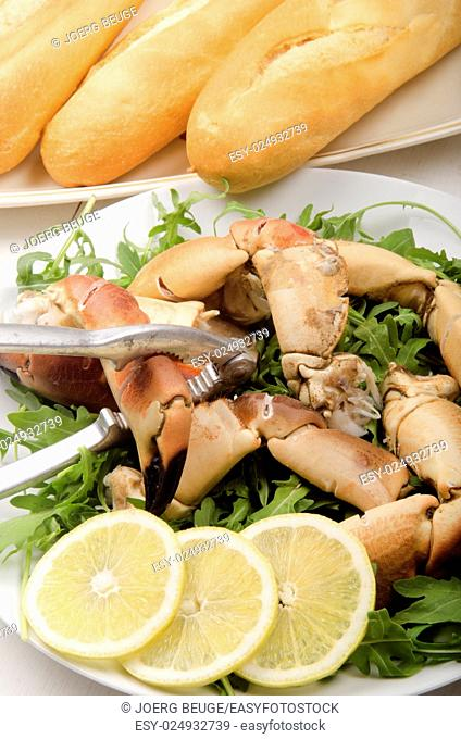 crab claw opened with a nutcracker, salad and bread roll