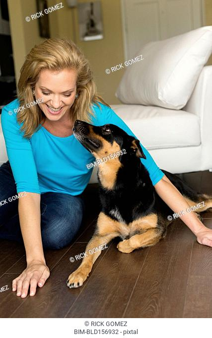 Caucasian woman playing with dog in bedroom