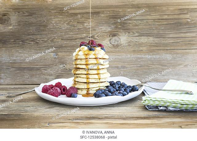 Pancakes with creamy cheese topping, garden berries and maple syrup