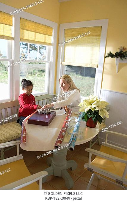 Mother and daughter wrapping gifts on kitchen table by large windows