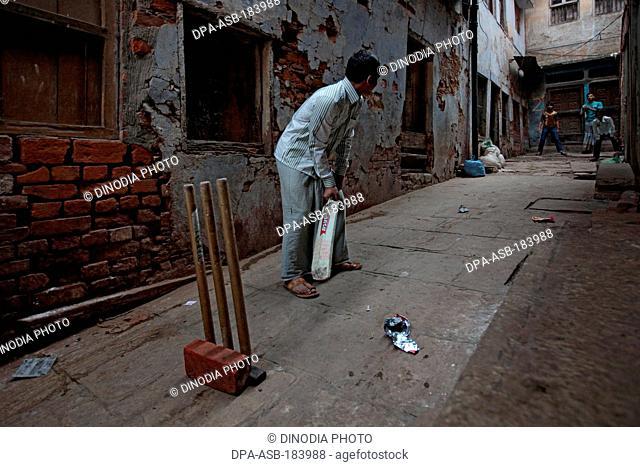 Young boys playing cricket in lane at Varanasi Uttar Pradesh India