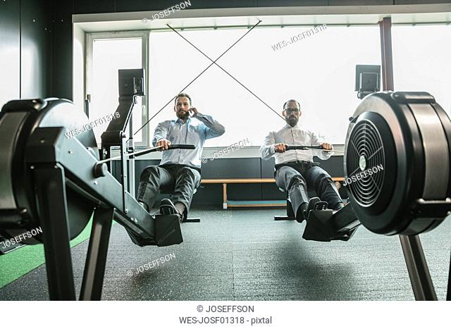 Businessmen training in gym, while making a phone call
