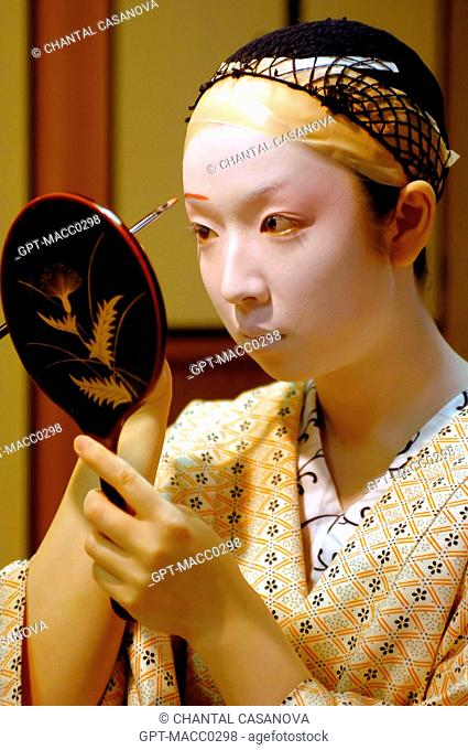 A GEIKO'S GEISHA TRADITIONAL MAKEUP DORAN, DRAWING THE EYEBROWS WITH RED MAKEUP, THE HAIR IS TIED BACK TO GO UNDER A WIG KATSURA, GION DISTRICT, KYOTO, JAPAN