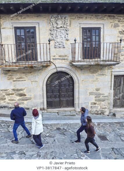 Four visitors on a walk through Puebla de Sanabria pass by a manor house with noble coat of arms on a street in Puebla de Sanabria. Zamora