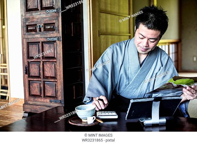 Japanese man wearing kimono sitting on floor in traditional Japanese house, using calculator and digital tablet